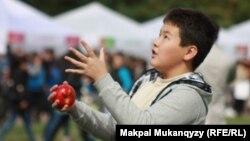 Мальчик жонглирует яблоками на фестивале в честь Дня города. Алматы, 21 сентября 2014 года.