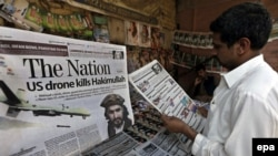 A man in Peshawar on November 2 reads newspapers carrying front-page headlines of the death of Hakimullah Mehsud.