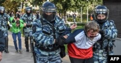 Russian National Guardsmen detain a man following a rally calling for fair elections in central Moscow on August 10.