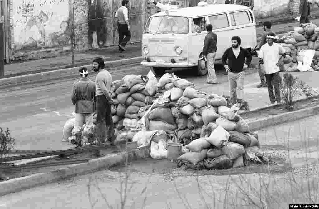 An ambulance passes sandbag roadblocks in Tehran to pick up the wounded from street clashes on February 10, 1979. A shootout between the army, air force cadets, and Khomeini followers left more than 60 people dead and hundreds injured.