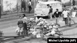სასწრაფო დახმარების მანქანა ქვიშის ტომრების საკონტროლო-გამშვებ პუნქტებს გადის, რათა თეირანის ქუჩაში შეტაკების დროს დაჭრილი აიყვანოს. 1979 წლის 10 თებერვალი. არმიას, საჰაერო ძალების კადეტებსა და ხომეინის მიმდევრებს შორის შეტაკებებს 60 ადამიანზე მეტი შეეწირა, ასობით მოქალაქე კი დაშავდა.