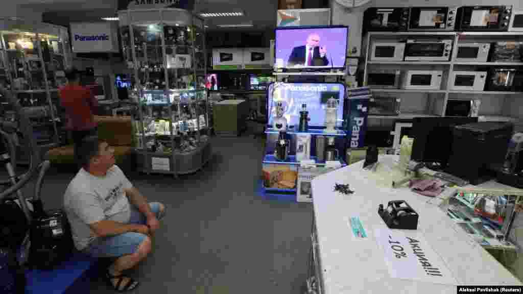 Мужчина смотрит ежегодную «прямую линию» с президентом России Владимиром Путиным в магазине бытовой техники и электроники в Евпатории