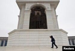 Мальчик идет вдоль монумента «Казах ели» с барельефом Назарбаева. Астана, 24 марта 2013 года.