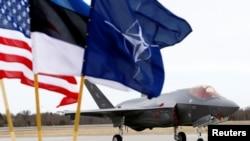 Флаги США, Эстонии и НАТО на фоне военного самолета на авиабазе в Эстонии.