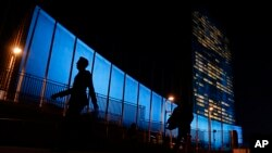Pedestrians walk by United Nations Headquarters, lit up in blue light, a day in advance of the 70th Anniversary of the U.N., Friday, Oct. 23, 2015, in New York. Around 200 other buildings and structures in 60 other countries were also lit in blue to comme