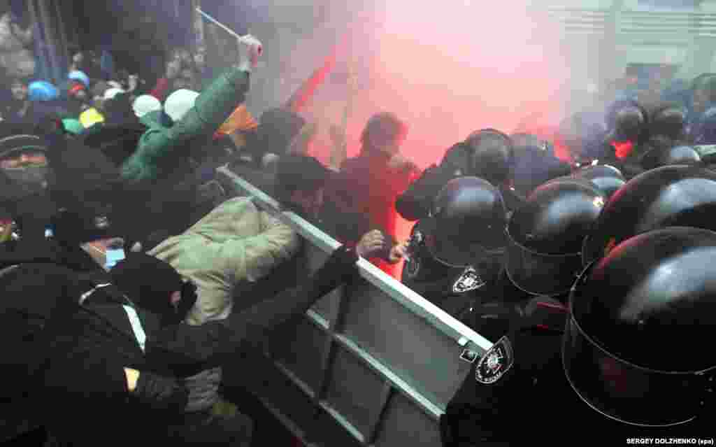 Protesters try to break through police lines close to the building of the presidential administration.