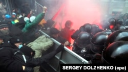 Protesters try to break through a riot police line near the presidential administration building during a rally by EU supporters in Kyiv on December 1.