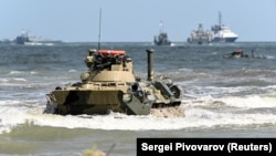 """DAGHESTAN -- A Russian BTR-82A armored personnel carrier drives onto the shore during the military exercises known as """"Centre-2019"""" at the range Turali on the Caspian Sea coast, September 20, 2019"""