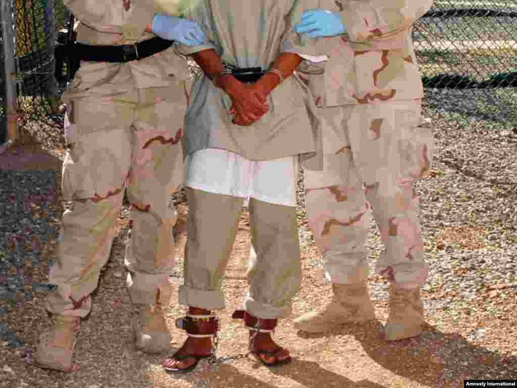 Guards escort a detainee to a medical facility at Guantanamo Bay.