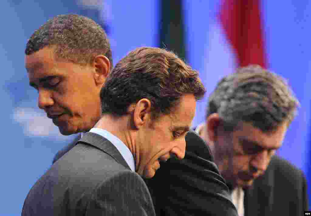 Obama turns the podium over to French President Nicolas Sarkozy as British Prime Minister Gordon Brown stands nearby at the G20 Summit in Pittsburgh, Pennsylvania, on September 25, 2009. The leaders addressed a previously secret Iranian nuclear facility, and demanded that Iran cooperate with international inspections of its nuclear sites.
