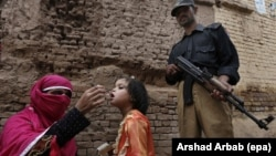 FILE: A polio worker administers polio vaccine to a child, in Peshawar, the provincial capital of Khyber-Pakhtunkhwa