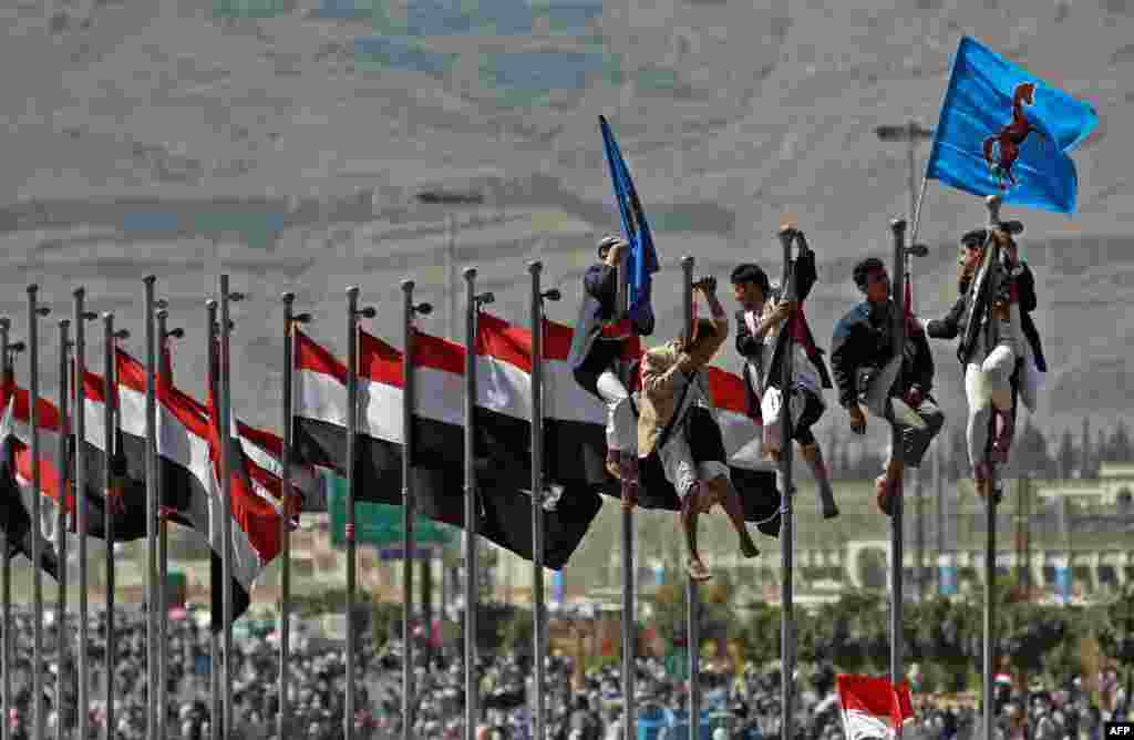 Supporters of former Yemeni President Ali Abdullah Saleh climb up flagpoles during celebrations on the occasion of the first anniversary of the handover of power in Sanaa. Saleh stepped down after 33 years at the helm in February 2011 and formally handed power to his then deputy, Abdrabuh Mansur Hadi. (AFP/Mohammed Huwais)
