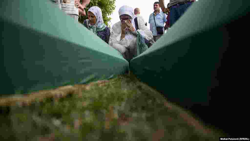 People mourn near coffins of their relatives, which are lined up for burial in Potocari near Srebrenica, July 10, 2017.