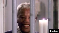 """1999 წლის 31 დეკემბერს, რობენის ციხეში გადაღებულ ამ ფოტოზე ნელსონ მანდელას სიმბოლური """"ათასწლეულის სანთელი"""" უჭირავს. ეს ის საკანია, რომელშიც მანდელამ არაერთი წელი გაატარა, როგორც პოლიტიკურმა პატიმარმა."""