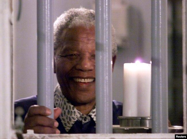 Нельсон Мандела тримає свічу через грати тюремної камери, в якій він був ув'язнений на острові Роббен-Айленд, 31 грудня 1999 року