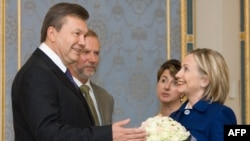 Ukrainian President Viktor Yanukovych (left) presents a bouquet of flowers to U.S. Secretary of State Hillary Clinton in Kyiv.