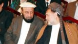Mohammad Khan (left) and Mohammad Mohaqiq talk during a gathering in Kabul in May 2014.