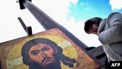 Иса пайғамбардың суретінің алдында тұрған әйел. Мәскеу, 30 қазан 2015 жыл. (Көрнекі сурет.)
