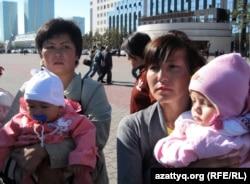 "Участницы акции ""Тасмағамбето, тастама"". На заднем плане задерживают мужчину. Астана, 25 сентября 2012 года."