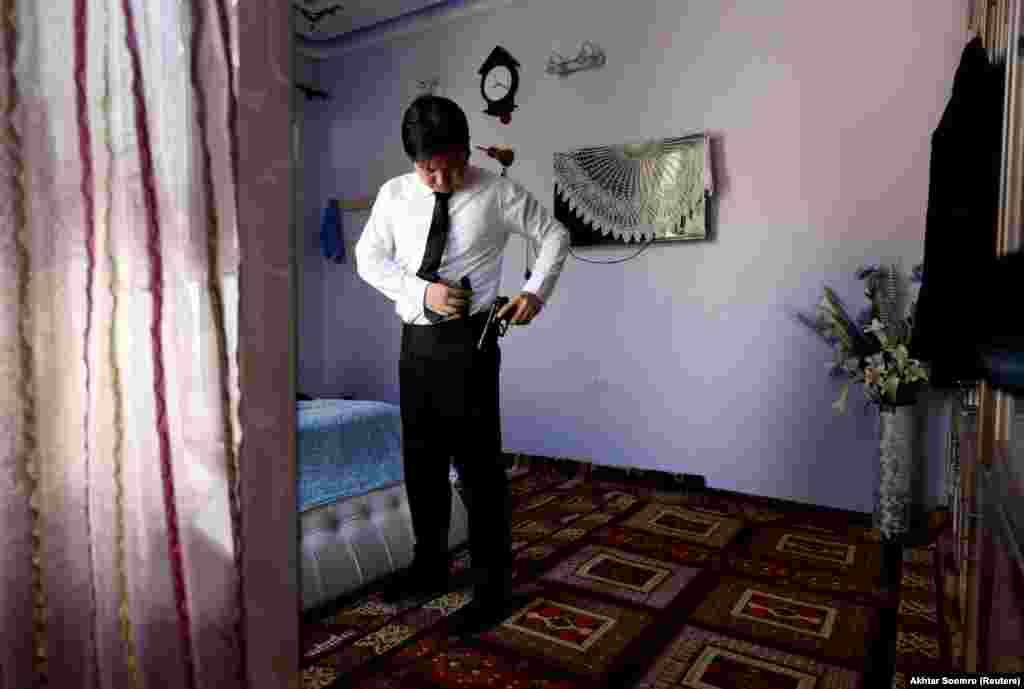 "Sardar Sahil, a Hazara lawyer and rights activist, packs his handgun before leaving his home in Hazara Town. He told Reuters: ""We are living under siege for more than 15 years due to sectarian attacks."""