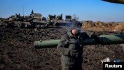 Боец украинской армии курит у своего танка. Донецкая область, 13 февраля 2015 года.