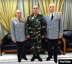 Микола Ткачов (ліворуч), міністр оборони Сирії Дауд Раджха (убитий у 2012 році) і генерал-майор Володимир Кужеєв. Скриншот з відео одного з сирійських антиасадівських угруповань, які поширювали неправдиве повідомлення про смерть Кужеєва.