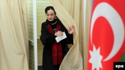 Azerbaijan -- A woman leaves a voting booth at a polling station in Baku, Azerbaijan, October 9, 2013