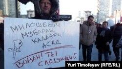 """Участник акции протеста в Москве держит плакат с надписью """"Милошевич. Мубарак. Каддафи. Асад. Вован, ты следующий!"""" Москва, 10 марта 2012 года."""