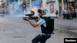 A plainclothes police officer fires plastic paintball gun pellets to disperse protesters in central Istanbul earlier this month.
