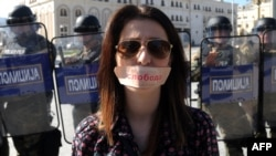 "Macedonia - A woman with a sticker on her mouth reading ""Freedom"" stands in front a police cordon during a protest in the center of Skopje on October 23, 2013. Journalists gathered there to protest the prison sentence of their colleague Tomislav Kezarovski."