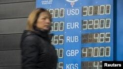 Женщина рядом с табло с курсами покупки и продажи валют частного обменного пункта. Алматы, 5 ноября 2015 года.