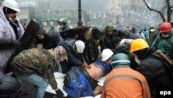 Активісти виносять пораненого товариша під час розстрілу спецпризначенцями людей на Майдані, 20 лютого 2014 року