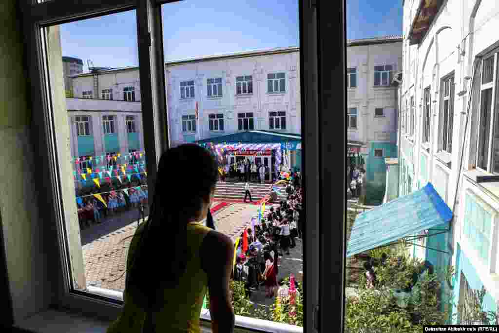 A girl watches a school graduation celebration on May 25 in Bishkek, Kyrgyzstan. (Beksultan Abibakir, RFE/RL)