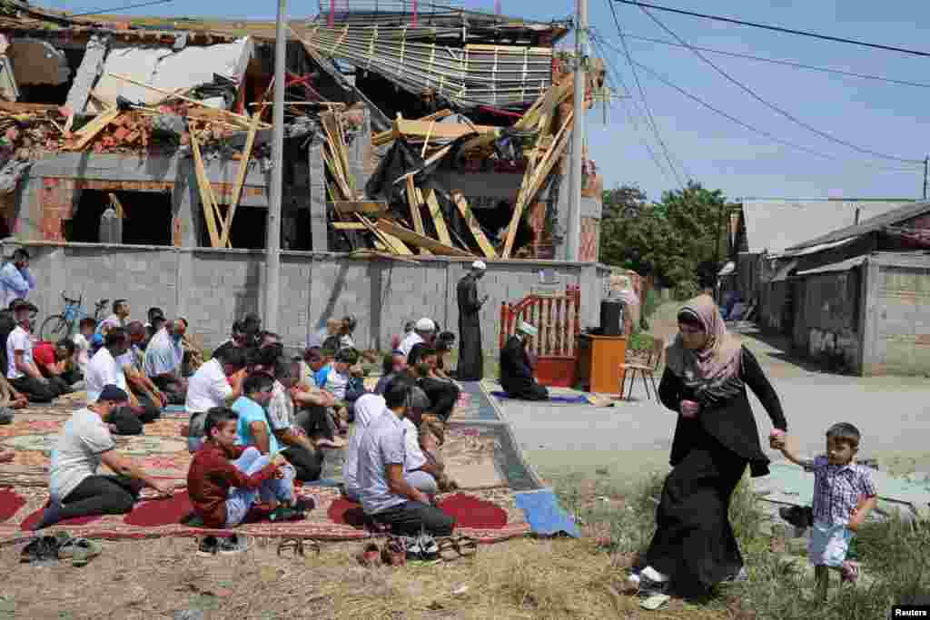 Muslims pray on a street in front of a destroyed, illegally built mosque in the Zemun Polje district of Belgrade, Serbia. (Reuters/Marko Djurica)