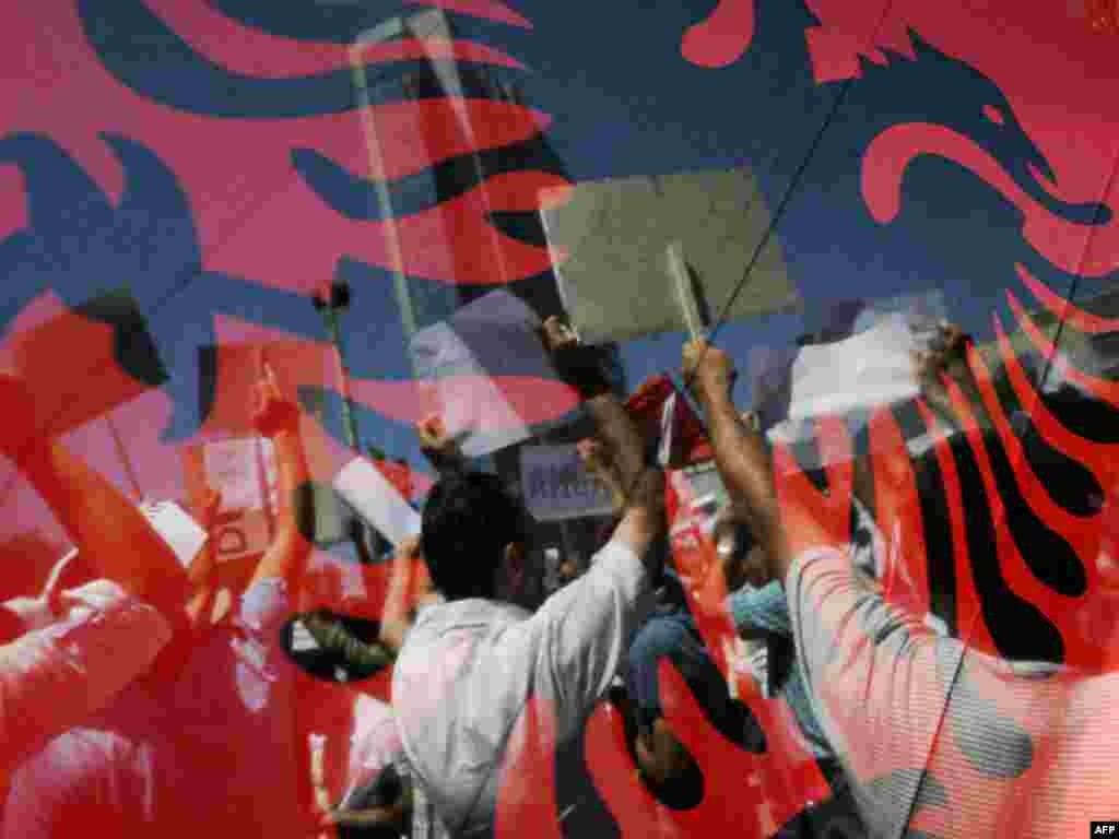 Kosovo Albanian men are seen through Albanian flags as they shout slogans during a protest in Pristina on June 22. Thousands of Kosovars turned out to demonstrate against widespread government corruption in the first significant social movement since Kosovo declared independence.Photo by Armend Nimani for AFP PHOTO