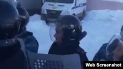 На фрагменте кадра из видео — сотрудники спецподразделения полиции на фоне полицейского микроавтобуса пытаются оттеснить толпу протестующих. Село Жансугурово, Аксуский район Алматинской области, 24 декабря 2019 года.
