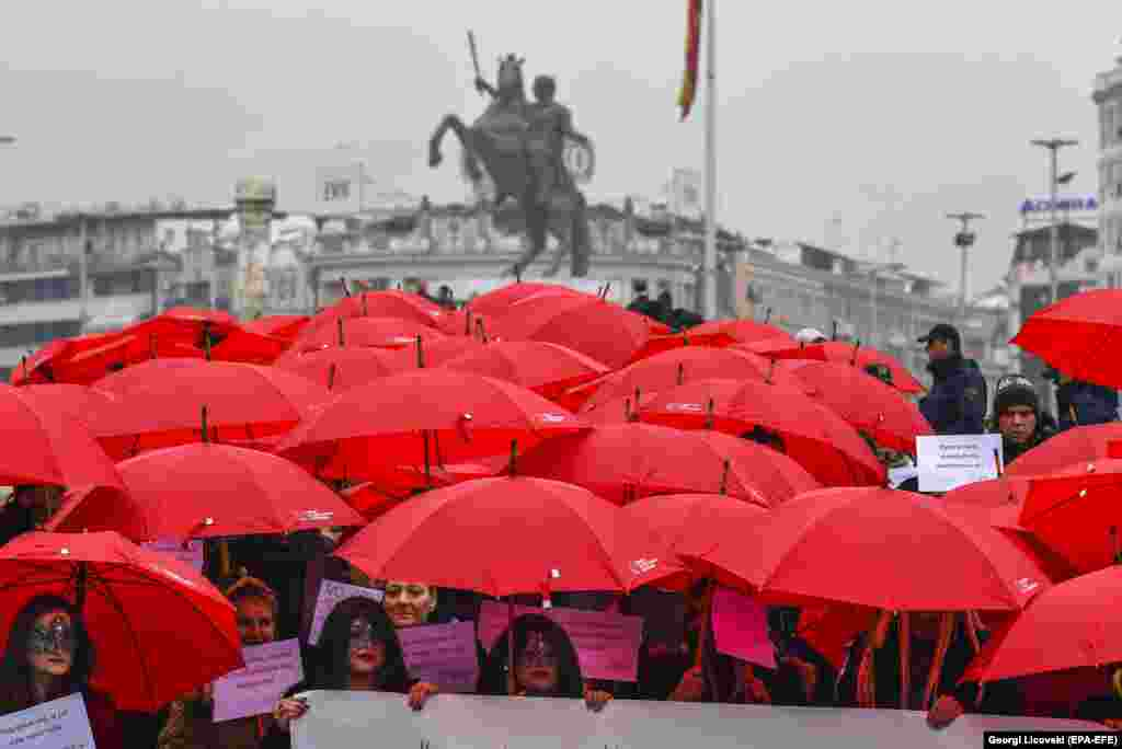 Macedonian sex workers carrying red umbrellas walk through the main square during a rally to mark the International Day to End Violence Against Sex Workers in Skopje on December 17. (epa-EFE/Georgi Licovski)