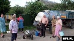 Луѓе полнат вода од цистерна