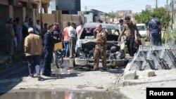 تکریت؛ شهروندان غیرنظامی همراه نیروهای امنیتی کنار خودرویی که در حمله نیروهای داعش سوخته است.