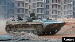 A fighter from Jabhat Fateh al-Sham, formerly the Al-Nusra Front, drives a tank through apartment blocks in southwestern Aleppo on August 5. The group used suicide sappers and tunnel bombs to break open the Syrian Army's battle lines and main defenses.
