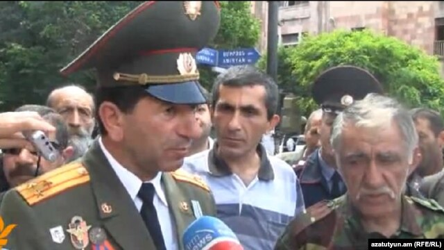 Armenia - Retired Colonel Volodya Avetisian (L) and other war veterans talk to journalists during a demonstration in Yerevan, 13May2013.