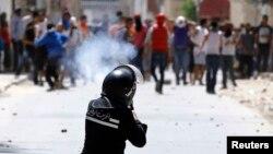 عنصر من شرطة مكافحة الشغب التونسية يطلق قنابل الغاز المسيلة للدموع بإتجاه محتجين في تونس العاصمة.