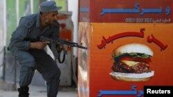 Афганский полицейский во время перестрелок в Кабуле 15 апреля