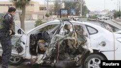Сотрудник иракских служб безопасности осматривает взорвавшийся автомобиль.