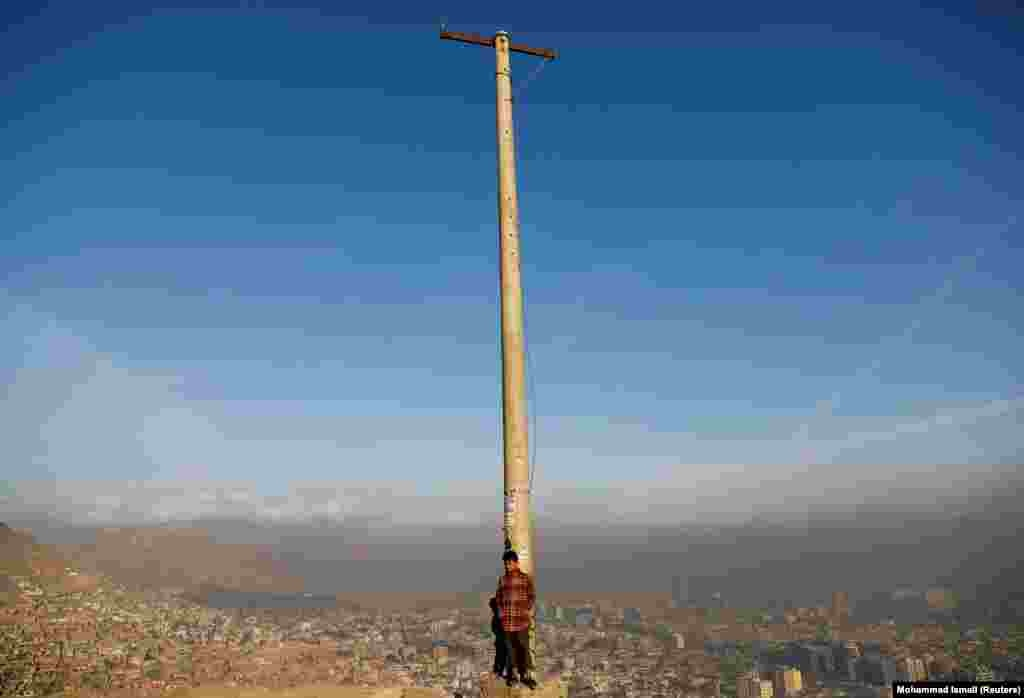 An Afghan boy stands in the sun on a hilltop overlooking Kabul. (Reuters/Mohammad Ismail )
