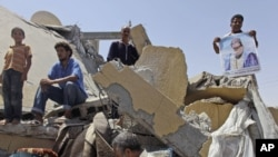 Libyans stand on the rubble of a home that was destroyed by a NATO bomb, allegedly killing two children and their mother in Zliten, in August 2011.