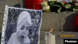 Armenia - A photographs of 6-month-old Seryozha Avetisian (L) is displayed during a candlelight vigil in Yerevan, 20Jan2015.