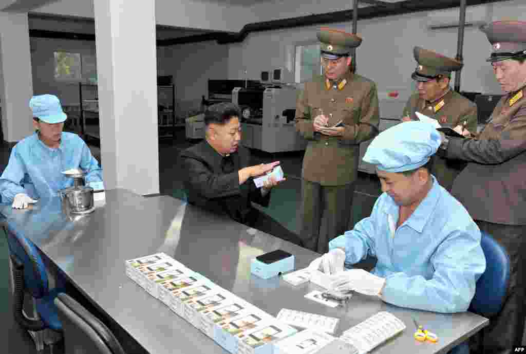 "North Koren leader Kim Jong-Un (center) inspects the production process for the new locally manufactured ""Arirang"" touch-screen mobile phone. (AFP/KCNA)"