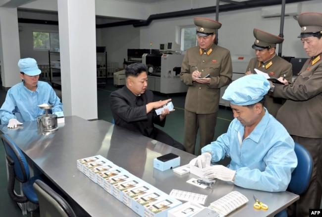 Кім Чен Ин дає вказівки на заводі з виробництва мобільних телефонів