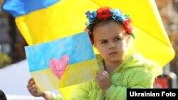 Дівчинка зі своїм малюнком на масовій акції у столиці України, яку проводили в час активних бойових на Донбасі. Київ, 4 жовтня 2014 року